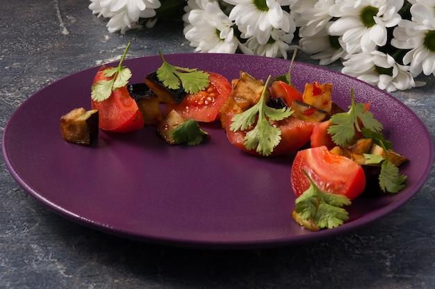 Leckerer salat aus frischen tomaten und gebratenen auberginen
