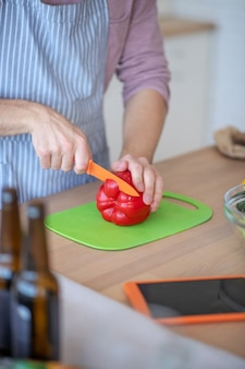 Leckerer salat. ein mann, der einen roten pfeffer für einen gemüsesalat hackt