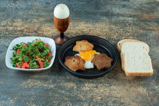 Leckerer salat mit geschnittenem brot und gekochten eiern auf marmorhintergrund