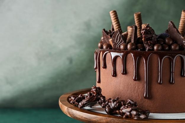 Leckerer schokoladenkuchen auf stand gegen farbe