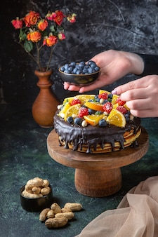 Leckerer schokoladenkuchen der vorderansicht, der mit frischem obst von frau auf dunkler wand verziert wird