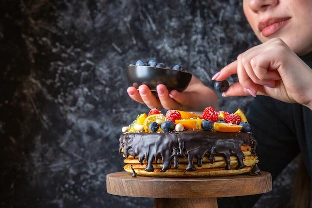 Leckerer schokoladenkuchen der vorderansicht, der mit früchten von frau auf dunkler wand verziert wird