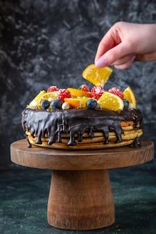 Leckerer schokoladenkuchen der vorderansicht mit frischen früchten auf dunkler wand
