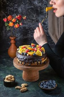 Leckerer schokoladenkuchen der vorderansicht mit frischen früchten, die von der frau an der dunklen wand gegessen werden