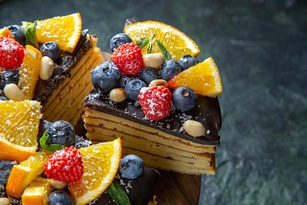Leckerer schokoladenkuchen der vorderansicht mit früchten auf dunkler wand
