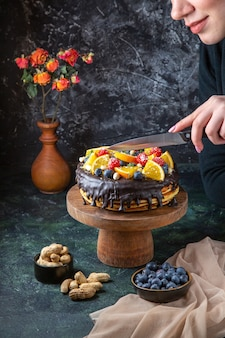 Leckerer schokoladenkuchen der vorderansicht mit früchten, die von frau auf dunkler wand geschnitten werden