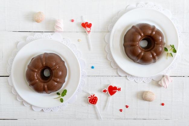Leckerer schokoladenpudding auf tellern auf einer weißen holzoberfläche. leichtes kalorienarmes dessert zum frühstück. draufsicht, flach liegen.