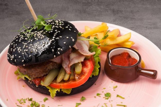Leckerer schwarzer burger mit rindfleischgemüse, dicker tomatensauce und pommes frites
