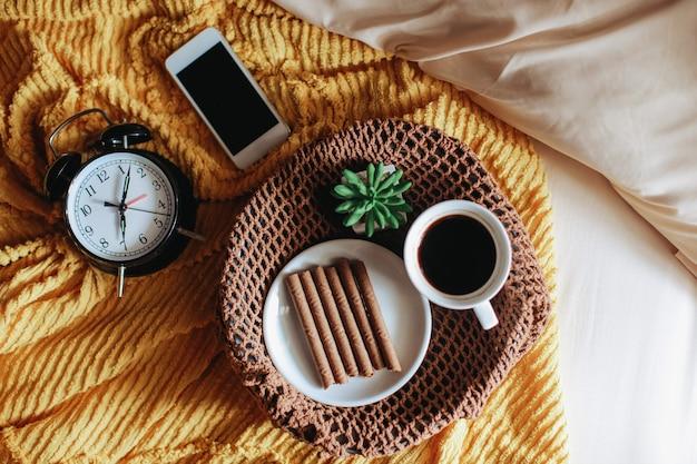 Leckerer snack und eine tasse kaffee zum frühstück mit uhr auf dem bett