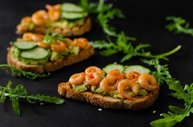 Leckerer snack von toast mit avocado, gebratenen garnelen, gurken und rucola