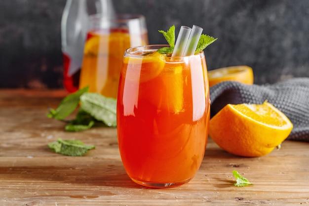 Leckerer, süßer, frisch gemachter, erfrischender sommercocktail mit orangen und minze, serviert in glas. nahansicht