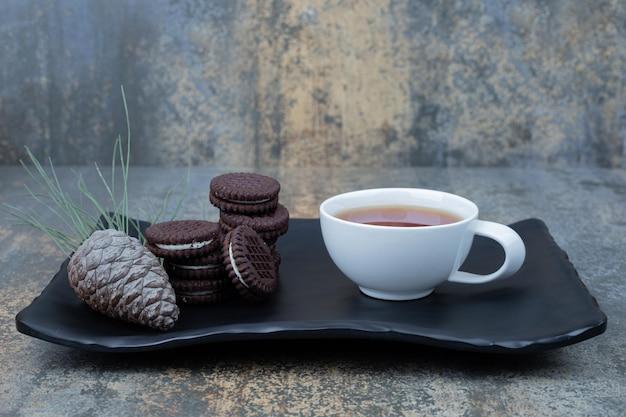 Leckerer tee in weißer tasse mit schokoladenkeksen und einem tannenzapfen auf dunklem teller.