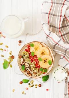 Leckerer und gesunder haferbrei mit äpfeln, granatapfel und nüssen. gesundes frühstück. fitness essen. richtige ernährung. flach liegen. draufsicht.