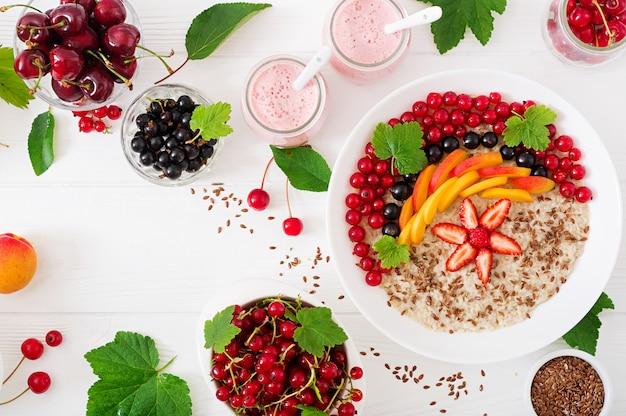 Leckerer und gesunder haferbrei mit beeren, leinsamen und smoothies. gesundes frühstück. richtige ernährung. draufsicht. flach liegen