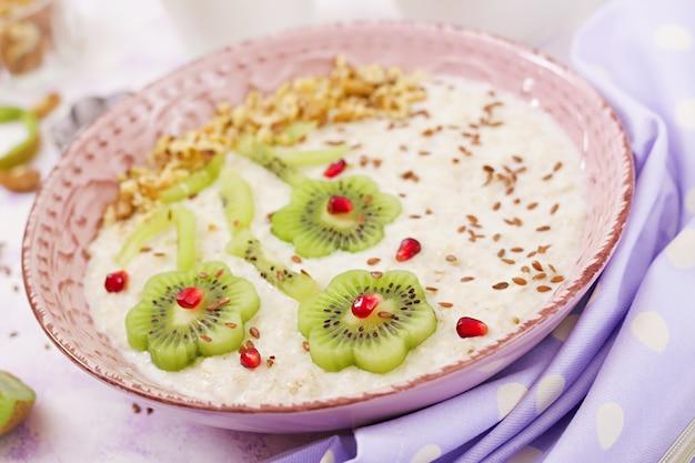 Leckerer und gesunder haferbrei mit kiwi, granatapfel und nüssen. gesundes frühstück. fitness essen. richtige ernährung.