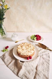 Leckerer und leckerer kuchen mit baiser und himbeeren auf einem teller