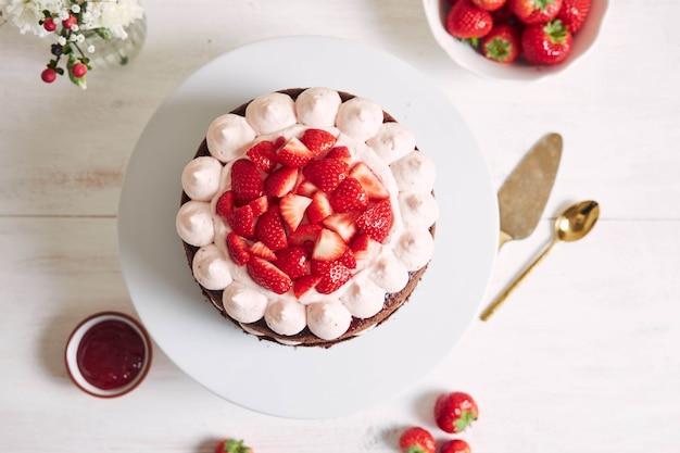 Leckerer und süßer kuchen mit erdbeeren und baiser auf teller