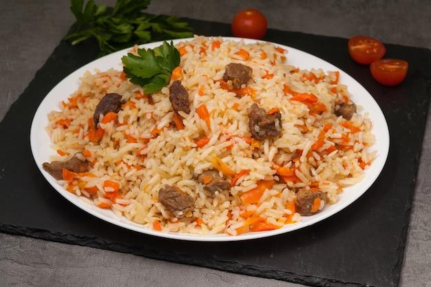Leckerer usbekischer pilaw mit rindfleisch auf einem weißen teller