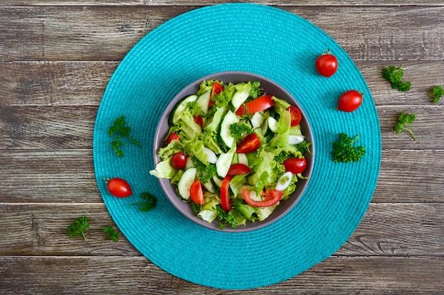 Leckerer vitamin-diät-salat mit frischen gurken, tomaten, gemüse. salat aus bio-gemüse. draufsicht, flach liegen.