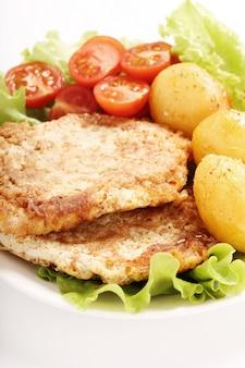Leckeres abendessen mit steaks, kartoffeln und salat