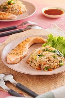Leckeres abendessen oder mittagessen, gesundes asiatisches essen. gegrillter lachs mit japanischem gebratenem reis und gemüse. lachs chahan reis auf holztisch
