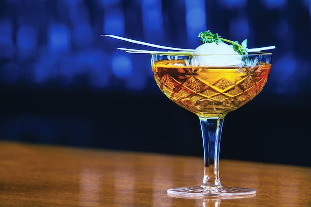 Leckeres alkoholgetränk mit großer eiskugel im inneren und kräutern. serviert in stilvollem glas.