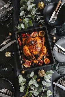 Leckeres, appetitliches gebackenes hühnchen serviert auf dekoriertem weihnachtstisch mit deko. ansicht von oben.