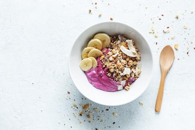 Leckeres, appetitliches, gesundes diätfrühstück mit müsli, blaubeerjoghurt und banane, serviert in einer schüssel. draufsicht.