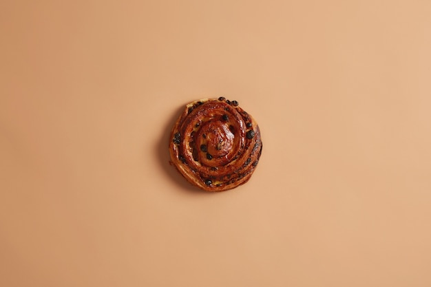 Leckeres, appetitliches, rundes, spiralförmiges, weiches brötchen mit rosinen, die in einer bäckerei gebacken wurden. kalorienreiches backprodukt mit viel fett und zucker. selbst gemachte rolle auf beigem studiohintergrund. süßes essen konzept.