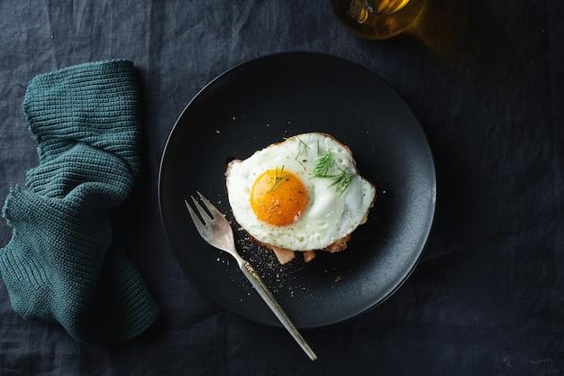Leckeres appetitliches sandwich mit hühnchenstücken und spiegelei, serviert auf teller auf dunkler oberfläche