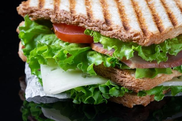 Leckeres appetitliches sandwich mit käse, tomaten und speck mit salat