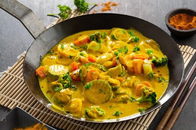Leckeres appetitliches veganes curry mit gemüse in der pfanne. nahansicht.