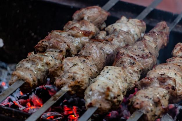 Leckeres barbecue, das auf einem feuer am spieß zubereitet wird beim picknick mit freunden