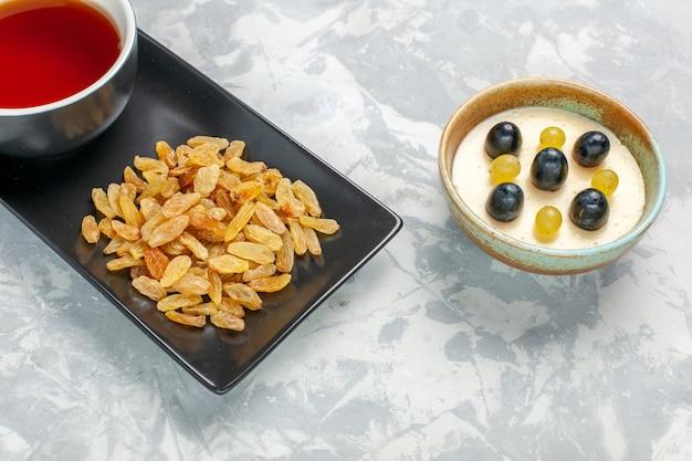 Leckeres cremiges dessert mit halber draufsicht mit einer tasse tee und rosinen auf der weißen oberfläche