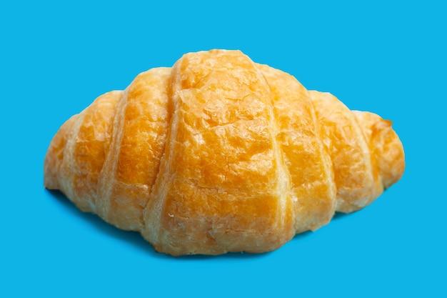 Leckeres croissant auf blauem hintergrund.