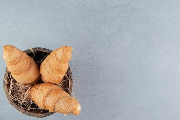 Leckeres croissant im eimer, auf dem marmorhintergrund. hochwertiges foto