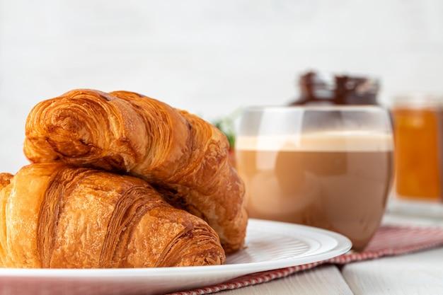 Leckeres croissant mit tasse kaffee mit milch auf küchentisch