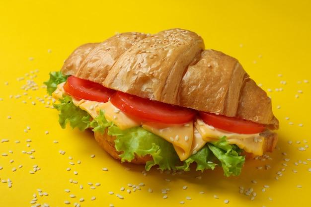 Leckeres croissant-sandwich auf gelb, nahaufnahme