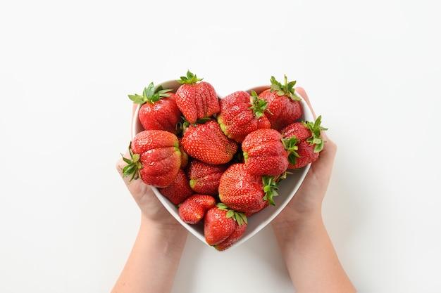 Leckeres dessert aus bio-erdbeeren aus eigenem anbau in kinderhänden in einem teller aus herz auf weißem hintergrund. konzept bio-produkte.