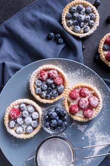 Leckeres dessert mit frischen blaubeeren und himbeeren auf einem großen grauen teller.