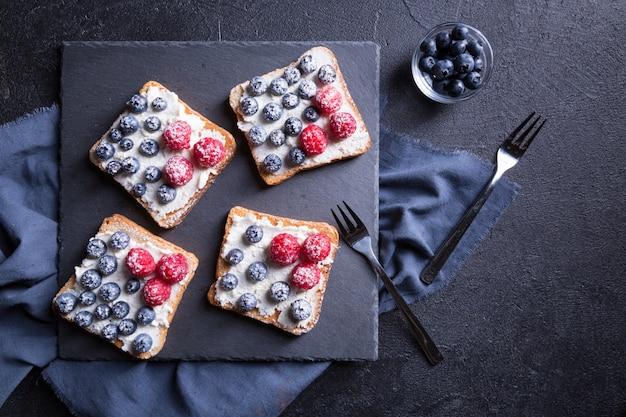 Leckeres dessert mit frischen blaubeeren und himbeeren auf einem schwarzen hintergrund.
