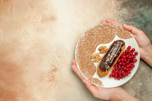 Leckeres eclair der draufsicht mit den roten beeren auf süßem kuchen-nachtisch des hellen tisches