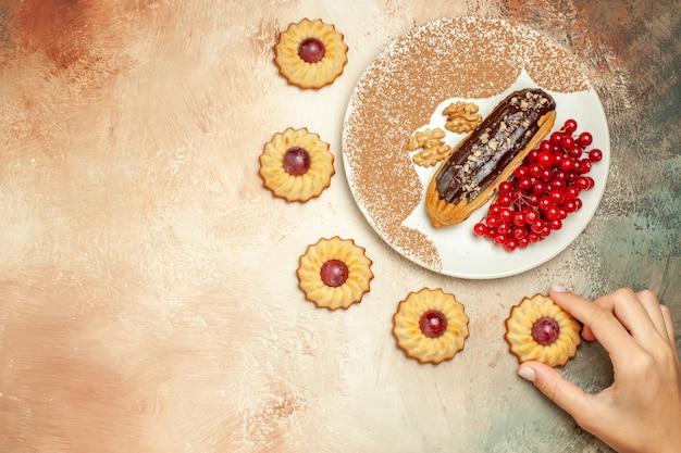 Leckeres eclair der draufsicht mit roten beeren und keksen auf dem hellen tischkuchen-nachtisch süß