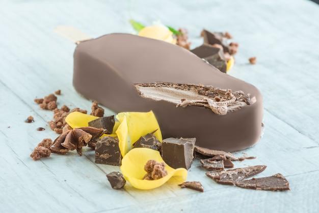 Leckeres eis in vollmilchschokolade mit gelben rosenblättern