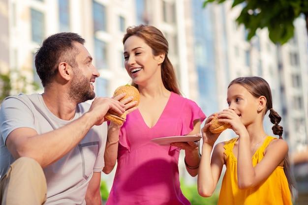 Leckeres essen. freudige glückliche familie, die leckere hamburger isst, während sie ihr picknick genießen