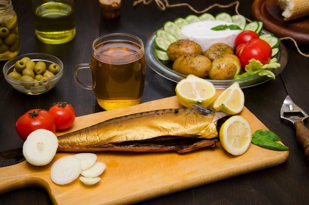 Leckeres essen geräucherte makrele und ein glas bier und andere produkte zum abendessen auf dem tisch