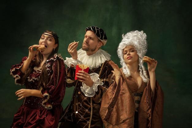 Leckeres fastfood. porträt der mittelalterlichen jungen leute in der weinlesekleidung auf dunklem hintergrund. modelle als herzog und herzogin, prinzessin, königliche personen. konzept des vergleichs von epochen, moderne, mode.