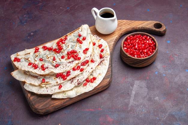 Leckeres fleisch qutabs pitas von halber draufsicht mit frischen roten granatäpfeln auf dunkelviolettem oberflächenfleisch-teig-pita