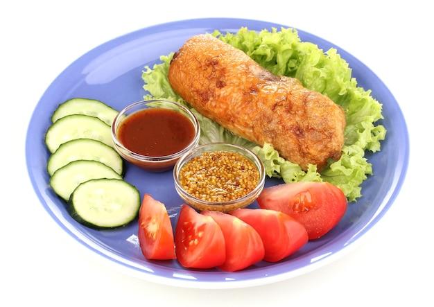 Leckeres fleischkotelett mit beilage auf platte lokalisiert auf weiß