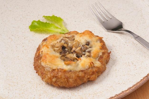Leckeres fleischkotelett mit zwiebeln, pilzen und käse